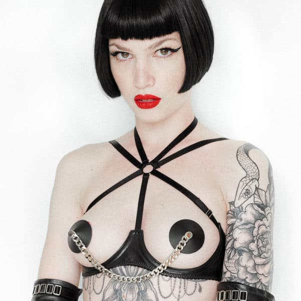Leather bra liquorice of the brand ELF ZHOU LONDON. The part that passes under the breasts of the model is in black leather, the bra is open on the breast area. There are three bands that cut the top of the bra: one that passes between the breasts and two others that start on the diagonal and join the back. She wears black nipples and both are connected by a silver chain. We can perceive the tattoos of the model as well as the beginning of the black leather gloves.