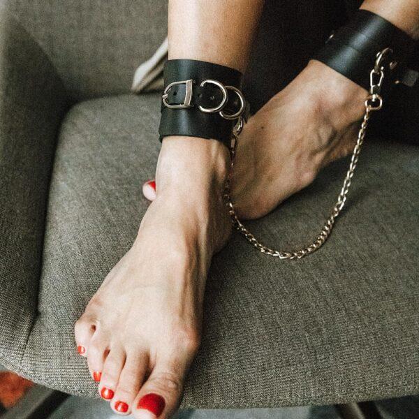 Menottes SENSUALITY ANKLE CUFFS ajustable en cuir noir pour cheville, avec des finitions en métal doré de MIA ATELIER chez BRIGADE MONDAINE