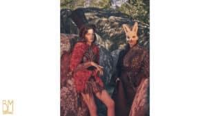 Deux personnes adossées contre des pierre en plein air femme avec un chapeau haut de forme noir et une robe avec perles rouges et noire à coté un homme avec un masque de lapin et un kimono noir avec des perles grises et le logo Brigade Mondaine sur un fond blanc