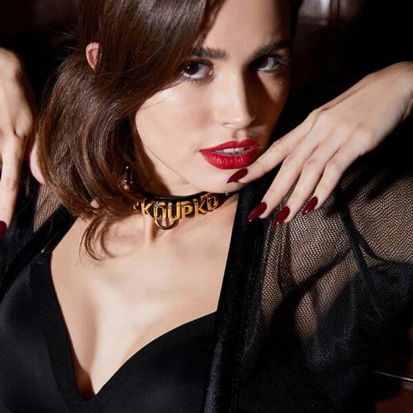 Petit collier noir de la marque UPKO avec les lettres formant le mot UPKO UPKO porté par une modèle en vue plongée en vue rapprochée plongeant avec le collier au centre et exposé ayant inspiré la collection UPKO X Brigade Mondaine