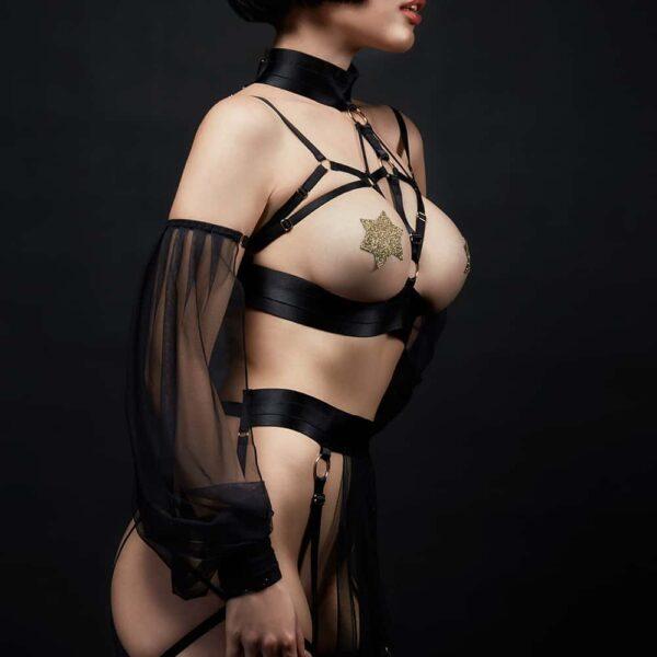 Costume Cleopatra de la marque Baed Stories. Ce costume comporte un soutien-gorge bandage ave des manches coulissantes. Une ceinture avec une longue pièce transparente et noire cache les parties intimes. De multiples laçages sont reliés à cette ceinture et enveloppent les jambes.