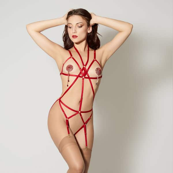 Signature Playsuit Bondage Red of the brand ELF ZHOU LONDON. The piece is open at the level of the breasts and passes around the neck to go along the length of the upper body. There is a central band of color wheel and two red bands that pass diagonally on both sides. At the level of the belt passes a red band, itself connected to two red bands that run diagonally along the upper thighs. She wears flesh-colored tights that reach the top of her thighs. She also has silver nippies red with rhinestones.