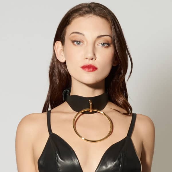 Leather Artefact Chocker O Black from ELF ZHOU LONDON. The chocker is black leather and has in the center of it a large gold buckle. The model has a black leather triangle support.