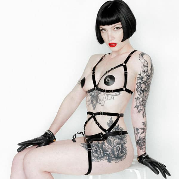 Leather Artefact Nippies Ring Bondage Black of the brand ELF ZHOU LONDON. With that the model wears a leather triangle support open on the breasts. She wears at the bottom a black harness that starts from the middle of her belly with a black band that runs horizontally and ends at the level of her thighs. The model wears leather gloves. She has many flowery tattoos. She is sitting on a white stool and looking at the camera.