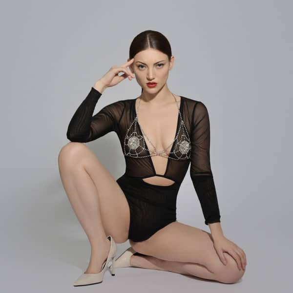 The model is wearing a crystal bra by ELF Zhou London. It is made of crystal nipple covers. Each breast has a spider's web with crystals to dress it up. The bra fastens at the neck and back.