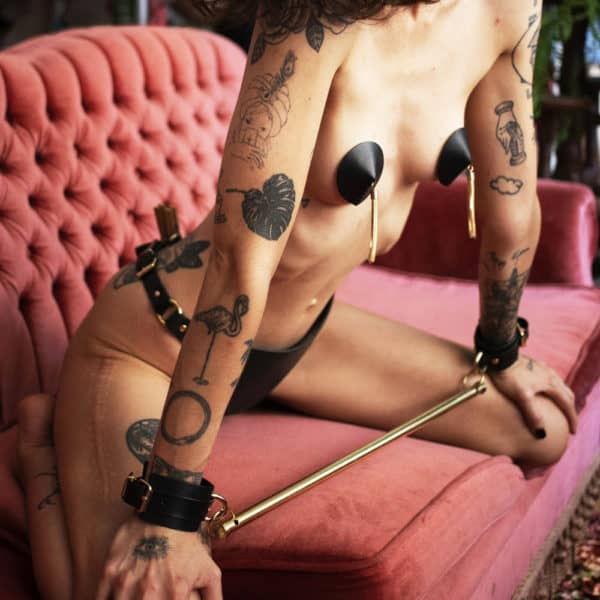 Spreader bar of the brand Elif Domanic. Two handcuffs with a gold colored buckle support a long and thin bar by two rings