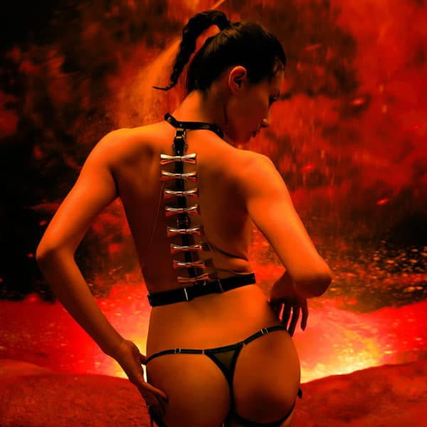 Black and gold 8 piece bondage set from Upko. The top is black and has gold colored bows on the back that go down the back. On both sides, there are gold chains that connect the top and bottom of the harness diagonally. The bottom is a black thong. In the back the background is red, the decor is an erupting volcano.